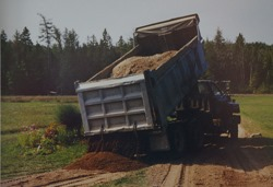 truck_dumping_gravel_for_connecting_driveway_loop