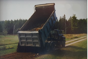 truck_with_chained_gate_spreading_layer_of_gravel